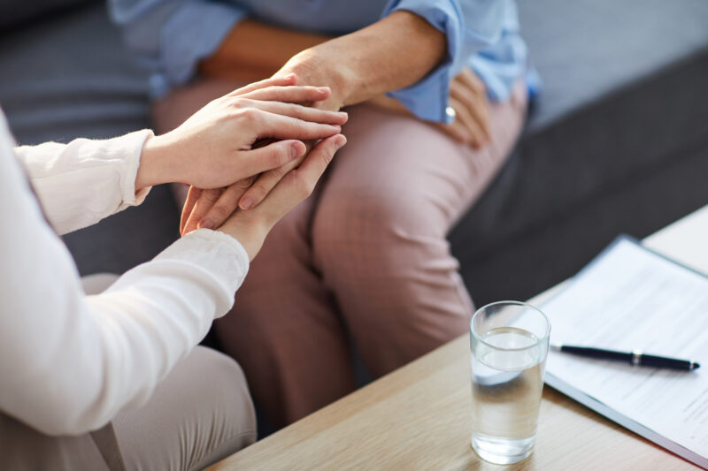 Young psychologist holding hand of her patient in need while consulting her after discussion of problem